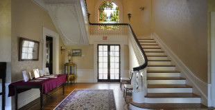 The grand staircase and stain glass window is a stunning  showcase for your event